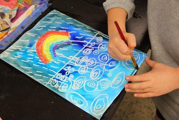 Дождик с радугой акварелью и восковыми карандашами Радугу и дождь рисуем восковыми карандашами. Затем слегка протираем рисунок влажной тряпочкой и по мокрому разрисовываем акварельными
